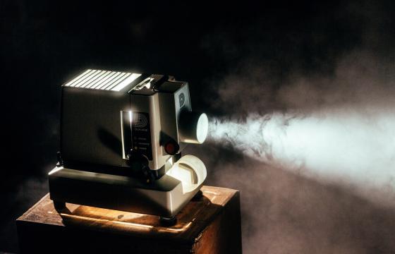Oude filmcamera die licht schijnt op het doek